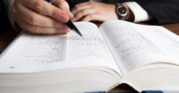 Na imagem, uma mão branca, com características masculinas, segura uma caneta preta em cima de um livro branco, aproximadamente de 1000 páginas (ou seja, muitas folhas). Uma mão segura a caneta sobre o livro, a outra, com um relógio de pulso, está apoiada sobre a mesa de madeira. No artigo, saiba como funcionam as etapas da tradução técnica.