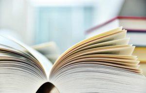 Imagem de um livro de aproximadamente mil páginas aberto ao meio. Ao fundo, desfocados, estão outros livros. Conheça as etapas da tradução técnica!