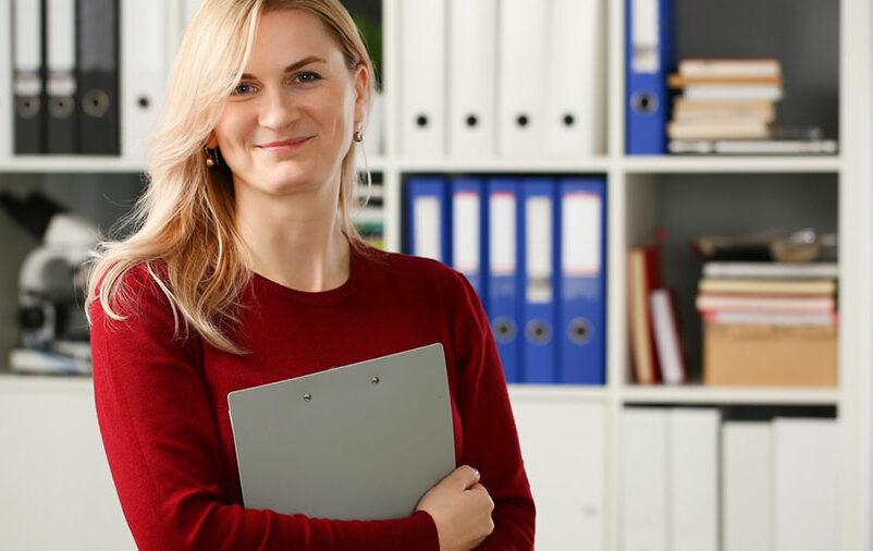 mulher loira segurando uma pasta em frente a estante de arquivos e sorrindo
