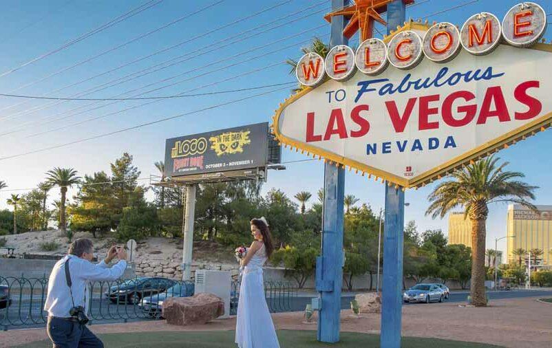 Na imagem, uma noiva tirando foto no ponto turístico de Las Vegas. Veja como funciona o casamento no exterior!