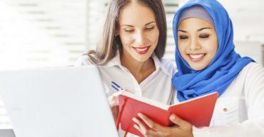 Cultura na tradução: mulher muçulmana mostrando um livro vermelho para tradutora