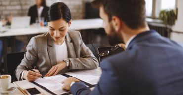 Mulher assinando documentos para abrir uma empresa no exterior