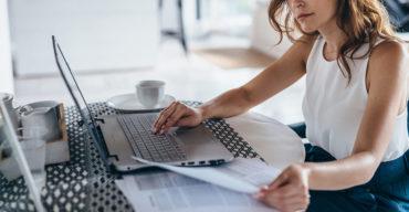mulher digitalizando documentos no notebook representando a relevância da tradução juramentada
