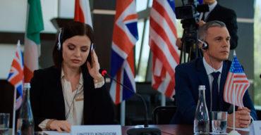 mulher com fone e microfone sentada em uma mesa focada na tradução simultânea