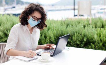 mulher de máscara e com notebook ensina com trabalhar no exterior