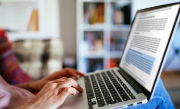 importância de revisar a tradução exemplificada pelo profissional com checando erros com o texto aberto no notebook